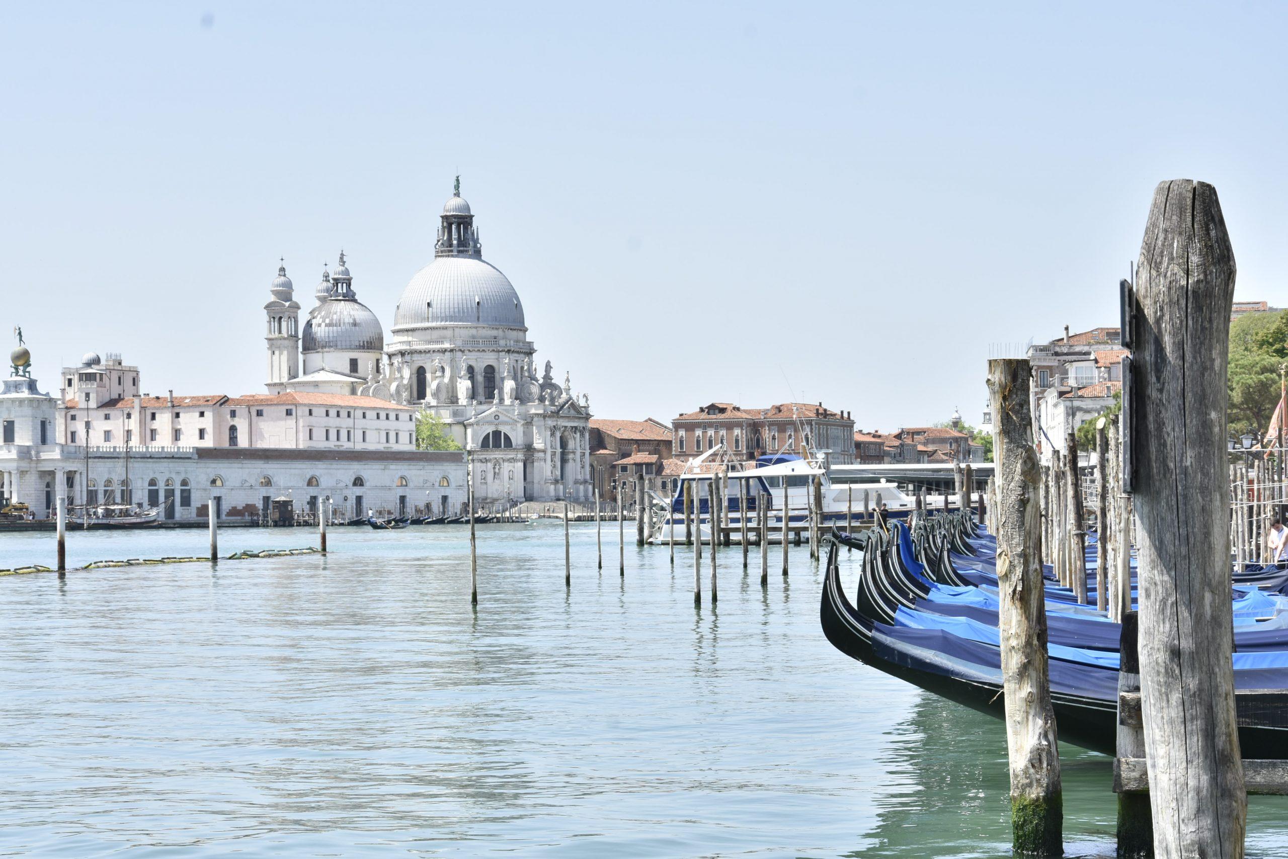 Venice skyline with gondolas and Punta della Dogana blue sky