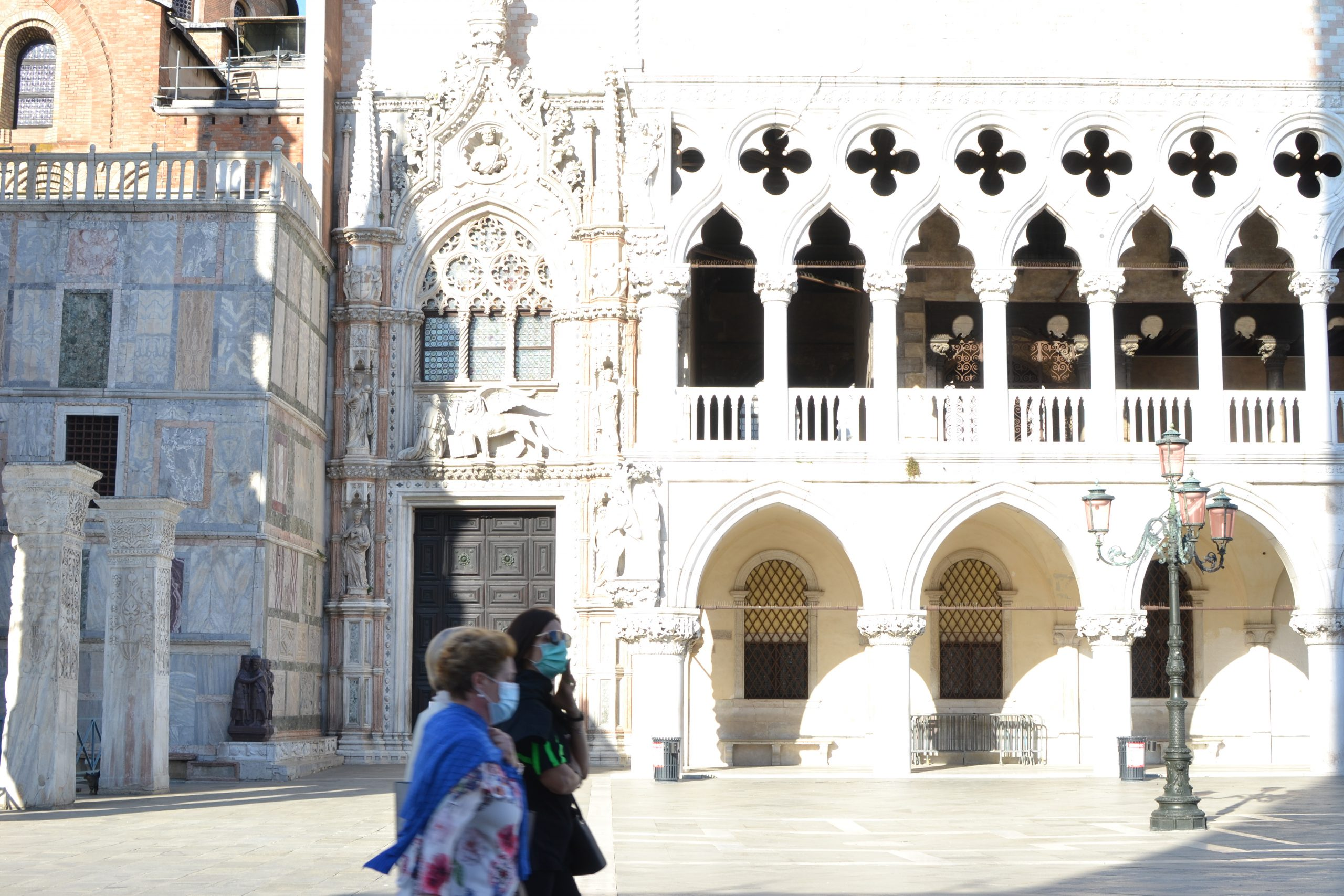 Doges palace facade with few people wearing face masks