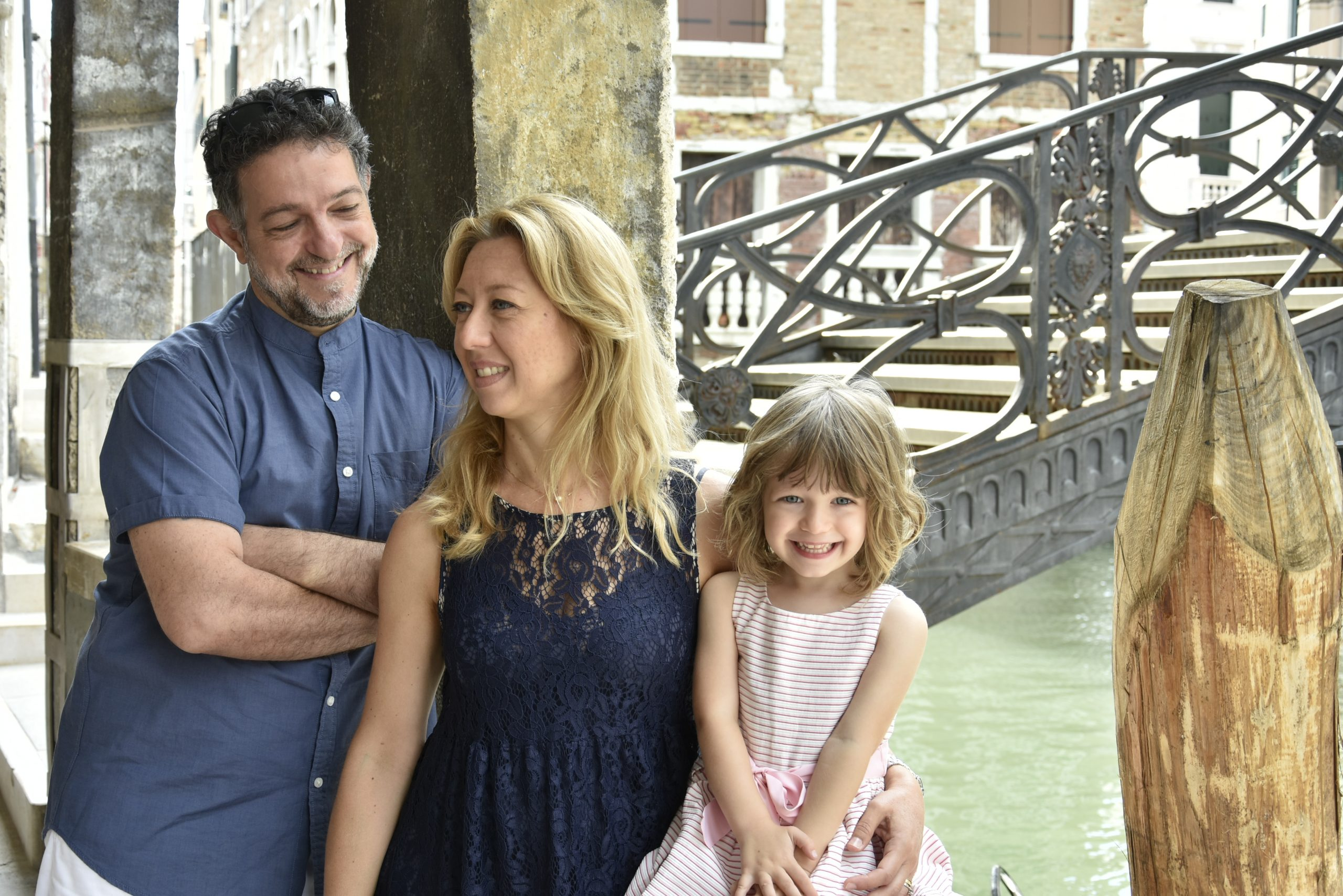smily family in Venice in front of a canal
