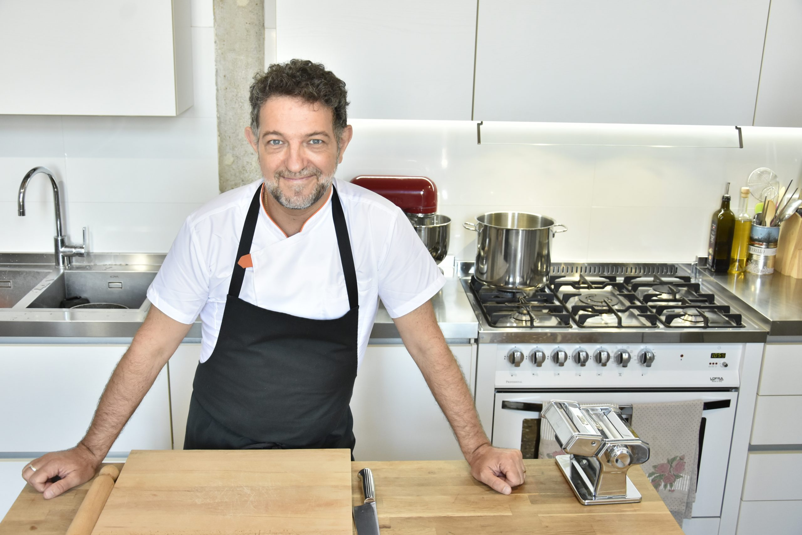italian chef stands in his kitchen