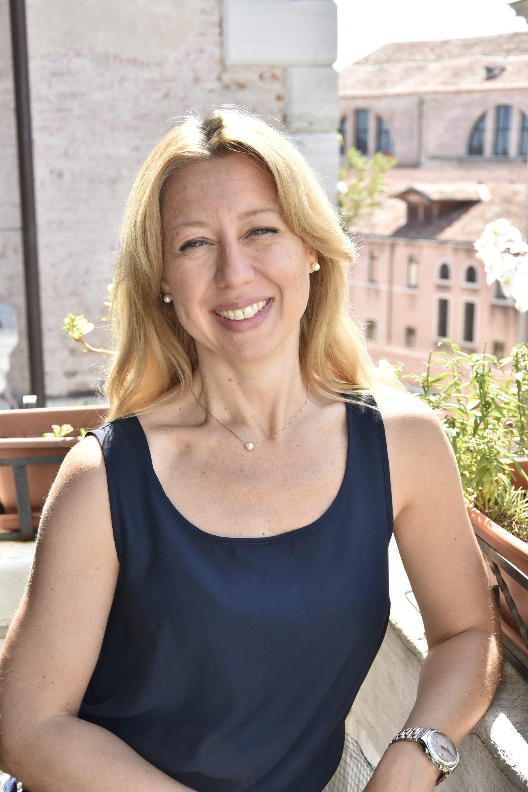 italian woman stands in her venetian balcony