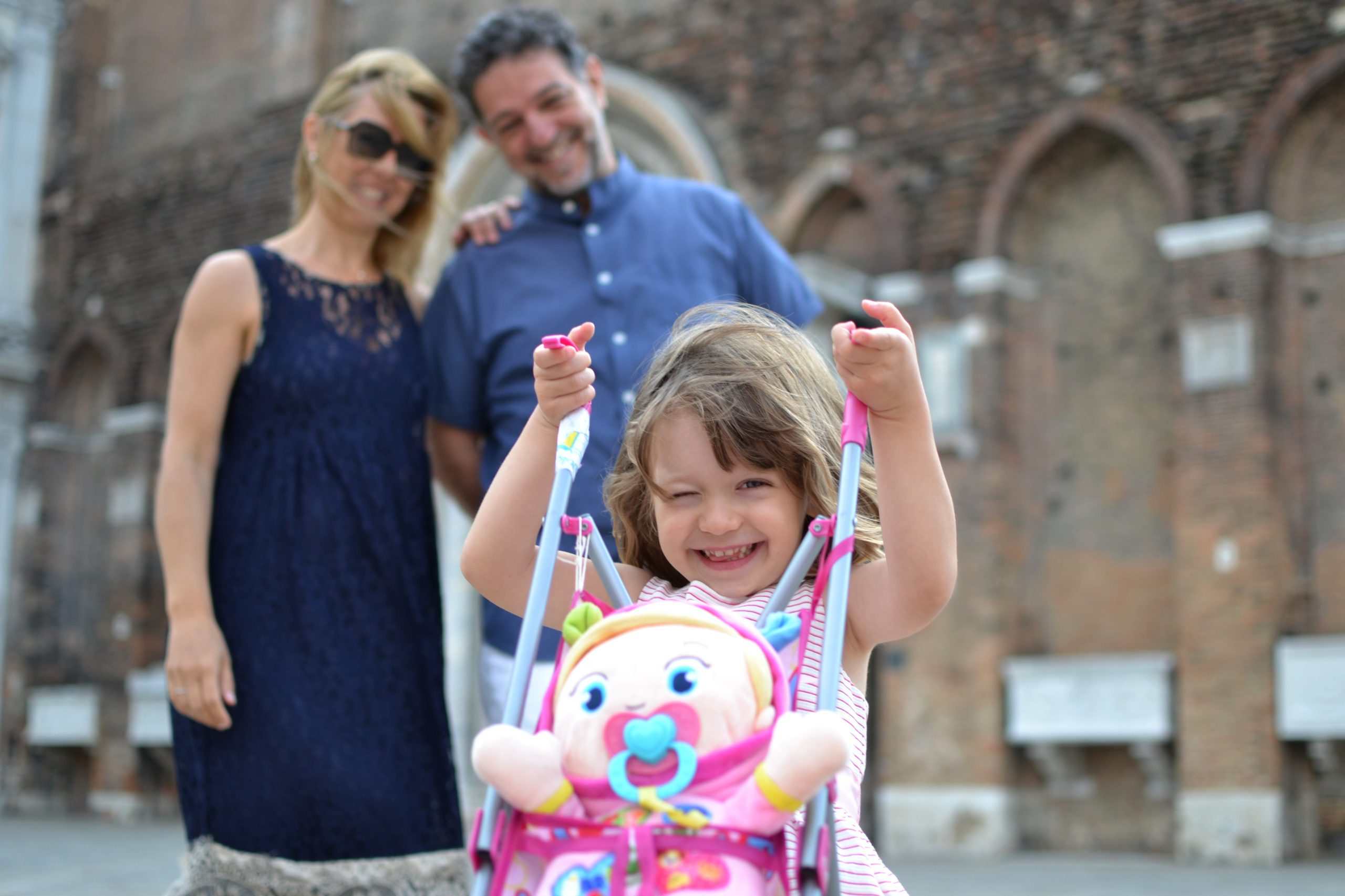 girl shows her doll family in front of a church in Venice