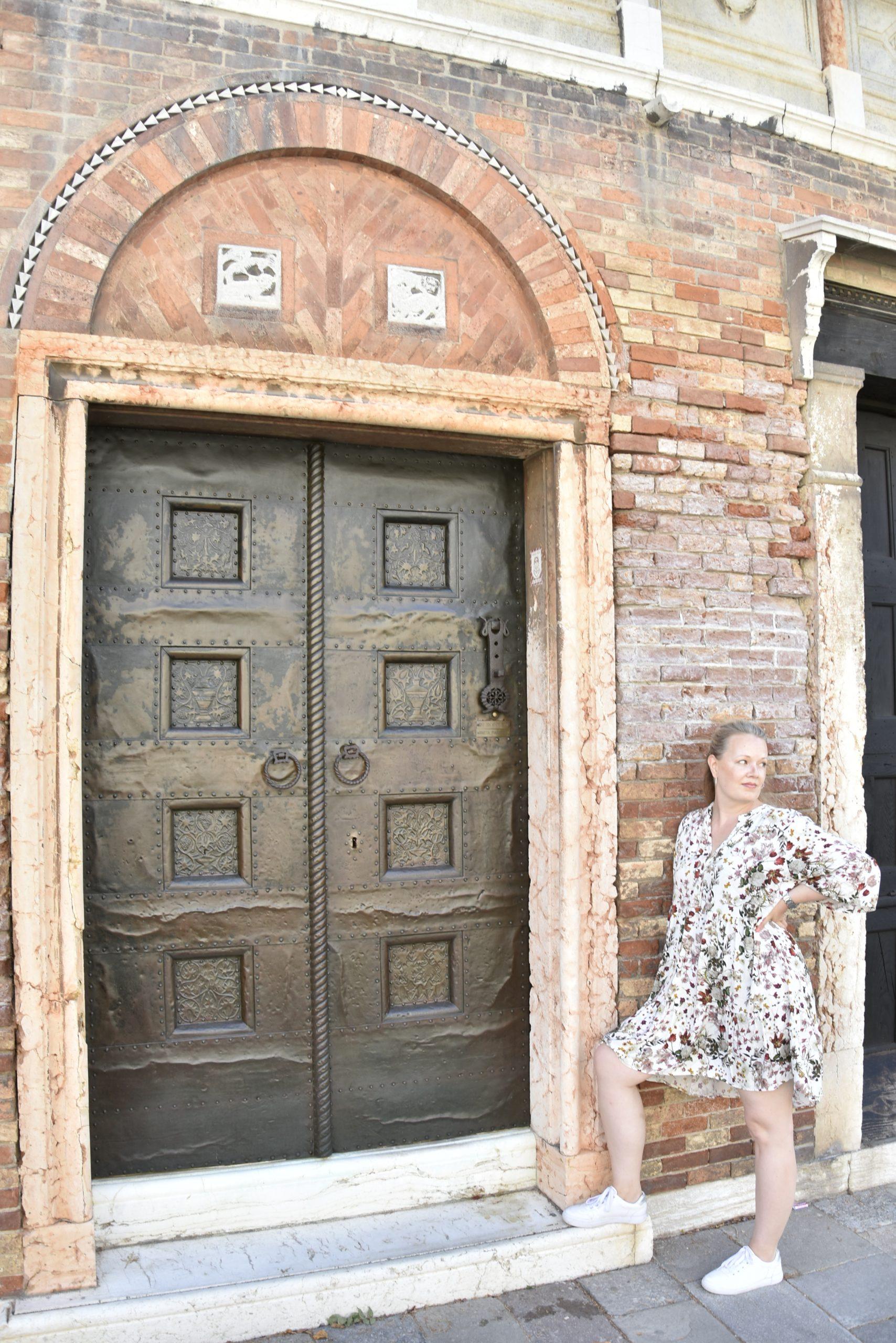 solo traveler in Venice in front of a historical door